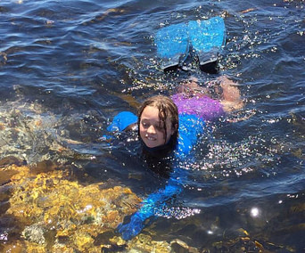A student swimming in a rockpool with flippers