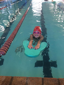 Elisabeth swimming with a kick board