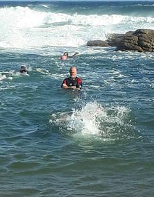 Coach Edward teaching students in the ocean