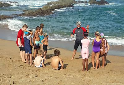 Coach Edward teaching students on the beach