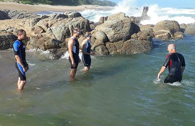Edward coaching adults in the ocean