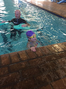 Edward in a pool with a student