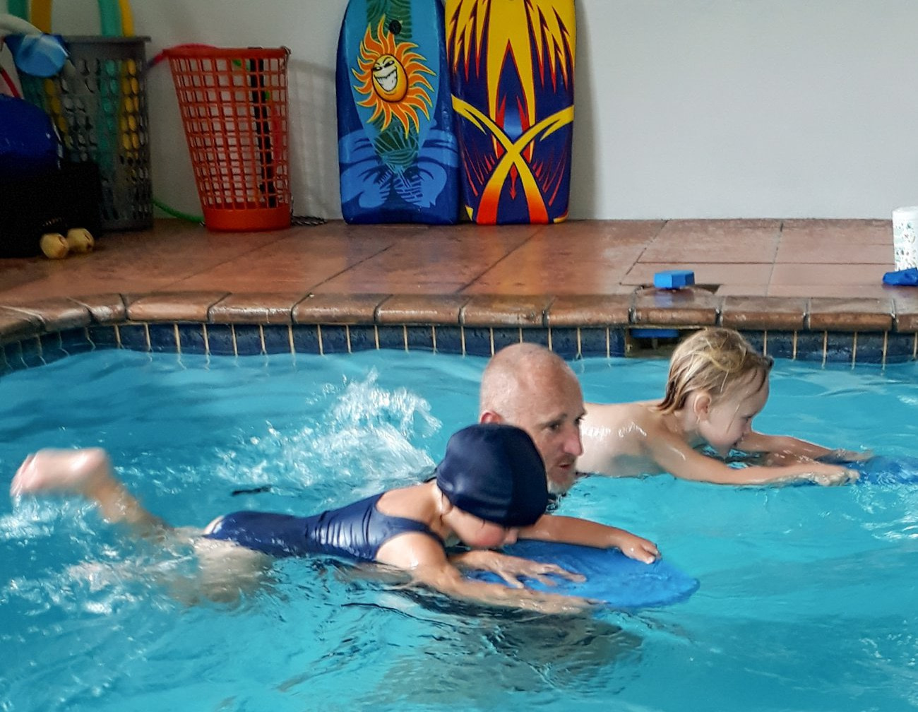 Edward in the pool with two student using kick boards