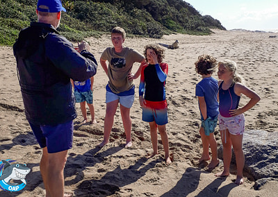 Coach Edward with students on the beach during the OAP session on 7 September 2019