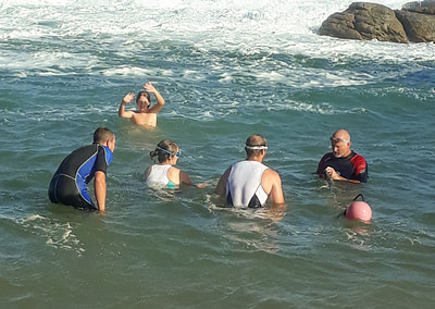 Coach Edward teaching students in the ocean