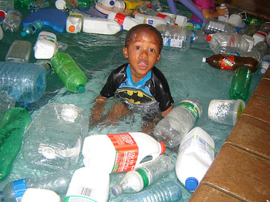 A student swimming with plastic bottles in the pool for the Green Peace #BreakFreeFromPlastic Project