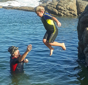Coach Edward watching as a student jumps into the tidal pool