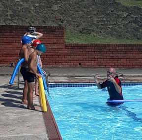 Edward coaching students in the outdoor pool