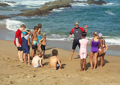 Coach Edward teaching students on the beach