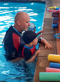 Coach Edward in the pool with young students