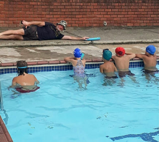 Coach Edward teaching young students in the outdoor pool
