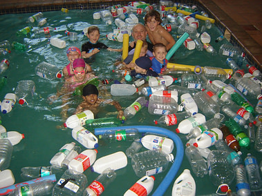 Coach Edward and students swimming with plastic bottles in the pool for the Green Peace #BreakFreeFromPlastic Project